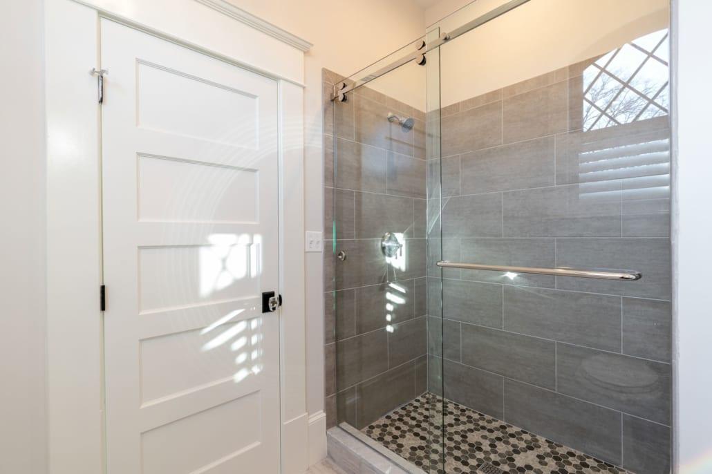 "Shower with sliding glass ""barn door""."