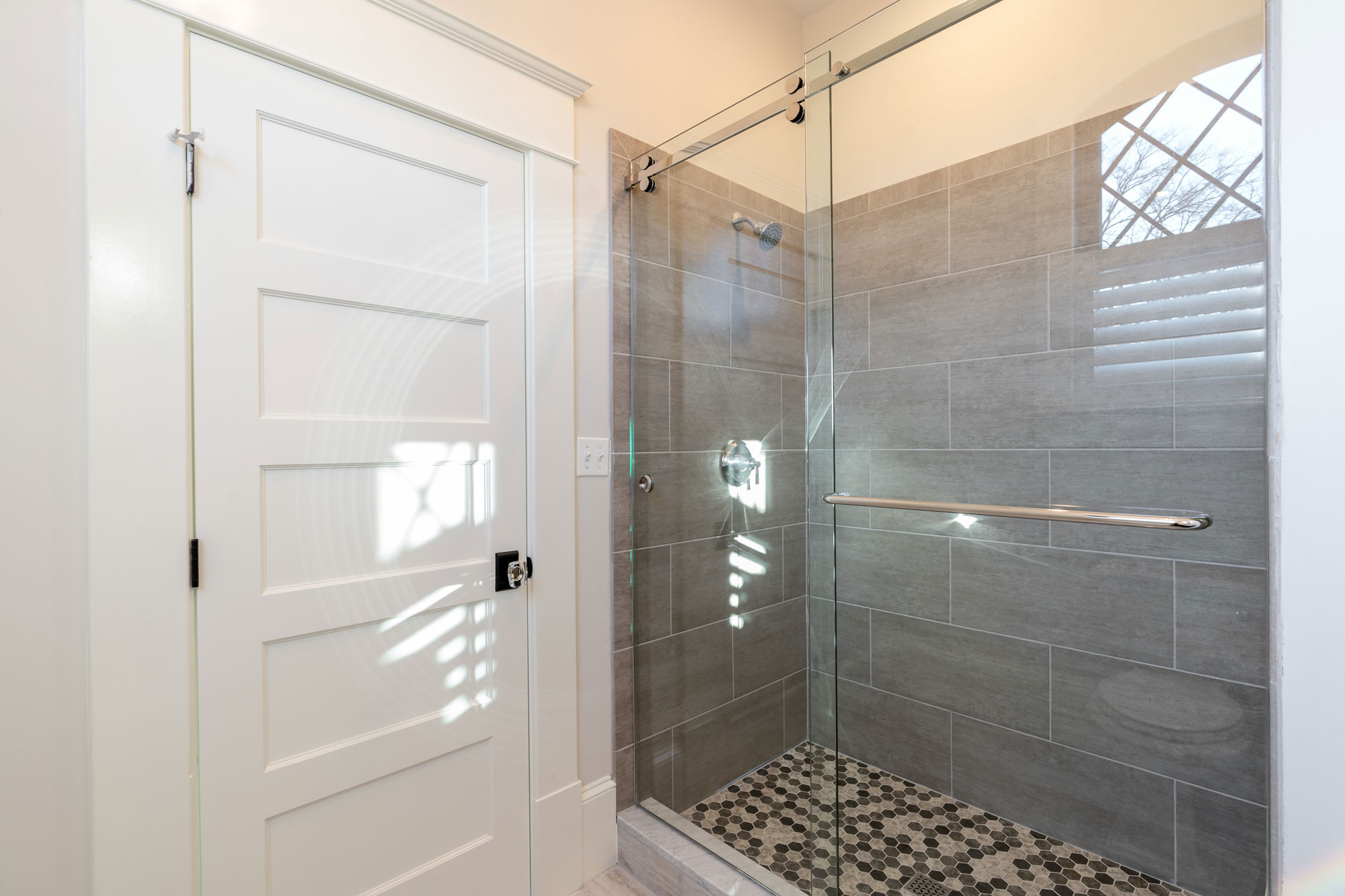 "Shower with sliding glass ""barn door""."