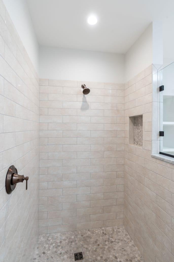 Basement bath shower with stone tiled floor.
