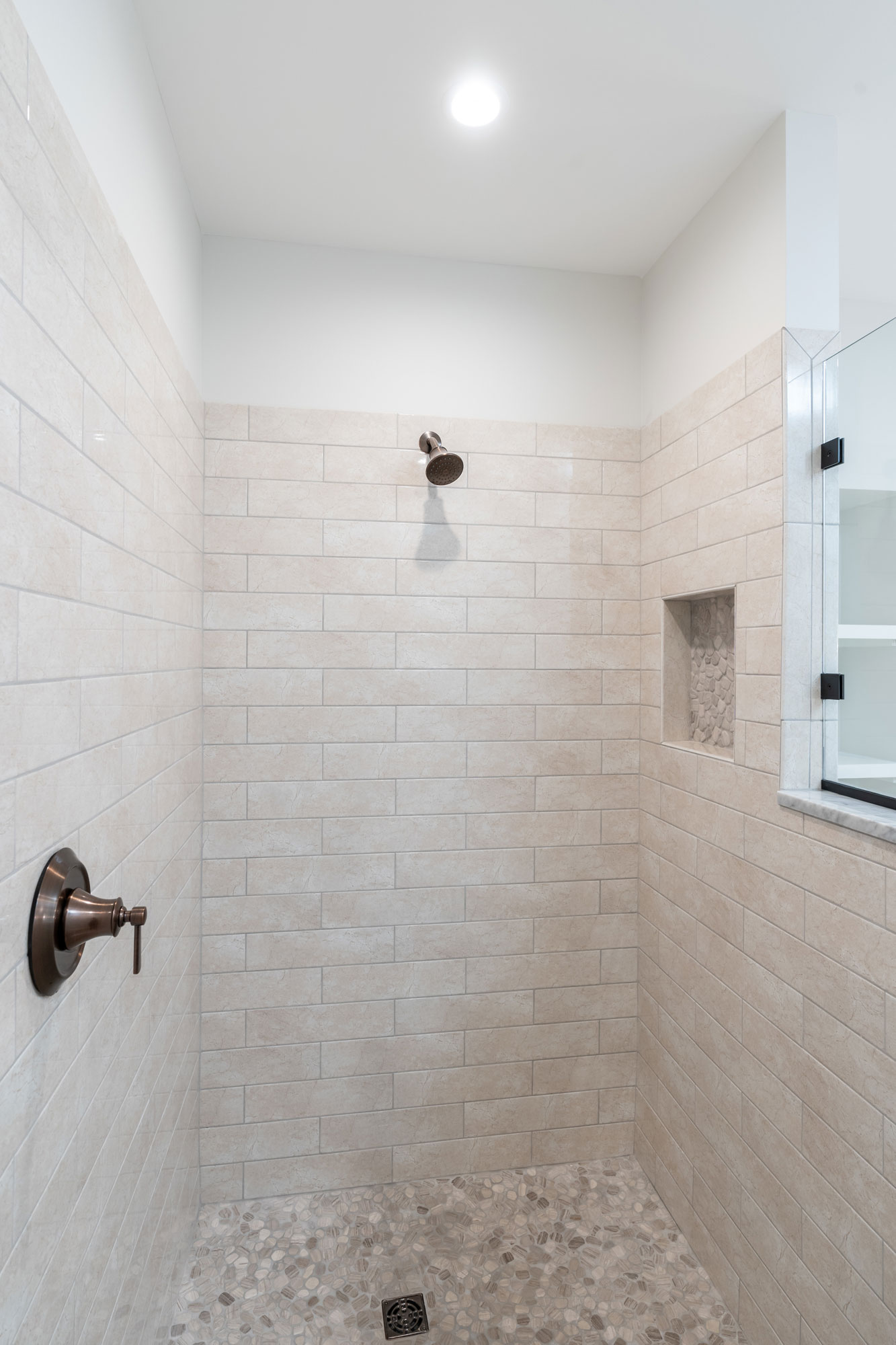 Basement bath shower with stone tiled floor.