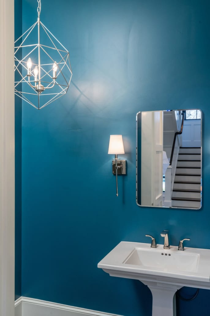A low hanging chandelier in the Powder Room reflects nicely on the walls.